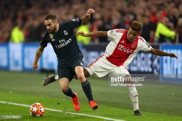 Daniel Carvajal of Real Madrid is challenged by David Neres of Ajax during the UEFA Champions League Round of 16 First Leg match between Ajax and...