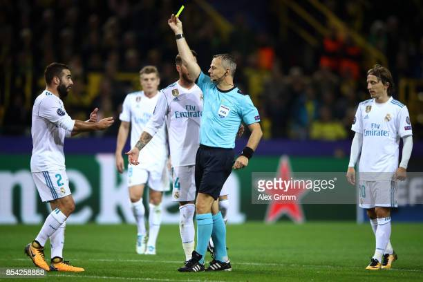 Daniel Carvajal of Real Madrid is shown a yellow card by referee Bjorn Kuipers during the UEFA Champions League group H match between Borussia...