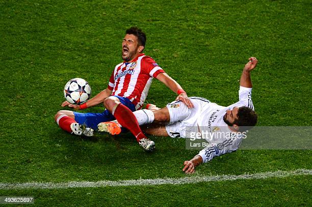 Daniel Carvajal of Real Madrid slides in to tackle David Villa of Club Atletico de Madrid during the UEFA Champions League Final between Real Madrid...