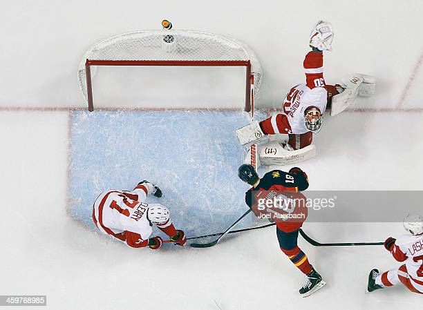 Daniel Cleary assists goaltender Jonas Gustavsson of the Detroit Red Wings defend the net against a shot by Shawn Matthias of the Florida Panthers at...