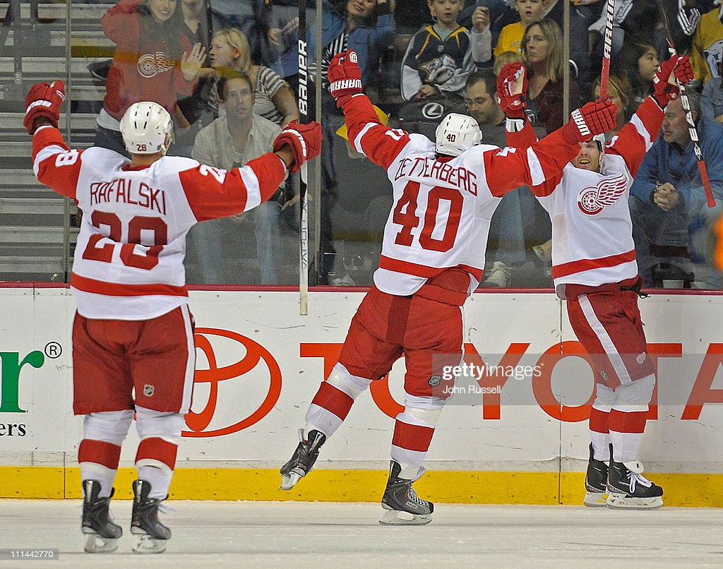 Daniel Cleary #11 celebrates his overtime game winning goal with Henrik Zetterberg #40 and Brian Rafalski #28 of the Detroit Red Wings against the Nashville Predators during an NHL game on April 2, 2011 at Bridgestone Arena in Nashville, Tennessee.