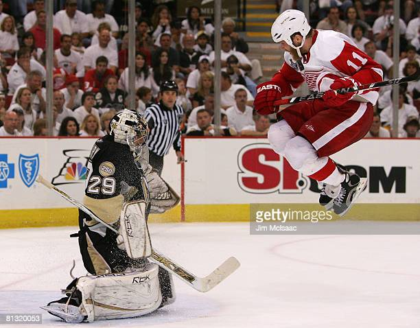 Daniel Cleary of the Detroit Red Wings leaps in the air as goaltender MarcAndre Fleury of the Pittsburgh Penguins makes a save during game four of...