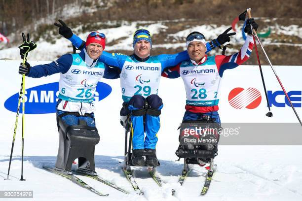 Daniel Cnossen of the United States second place Maksym Yarovyi of Ukraine first place and Eui Hyun Sin of Korea third place pose for photographers...