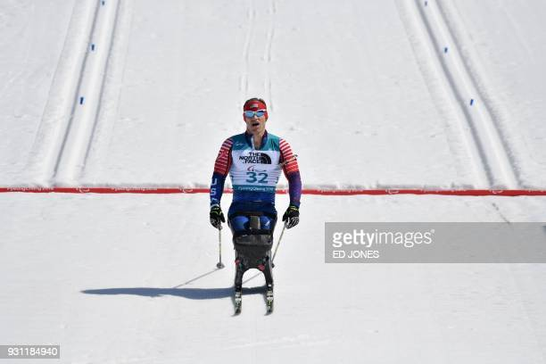 Daniel Cnossen of the US crosses the line to finish second in the men's 125km sitting biathlon event at the Alpensia Biathlon Centre during the...
