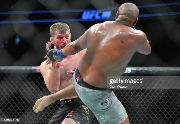 Daniel Cormier kicks Stipe Miocic during their heavyweight championship fight at TMobile Arena on July 7 2018 in Las Vegas Nevada Cormier won by...