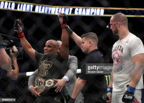 Daniel Cormier left celebrates his defeat of Volkan Oezdemir by knockout for the light heavyweight championship belt during UFC 220 at TD Garden in...