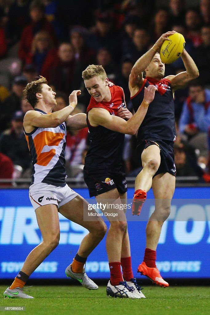 Daniel Cross of the Demons (R) marks the ball but gets taken off by stretcher after this incident during the round 23 AFL match between the Melbourne Demons and the Greater Western Sydney Giants at Etihad Stadium on September 6, 2015 in Melbourne, Australia.