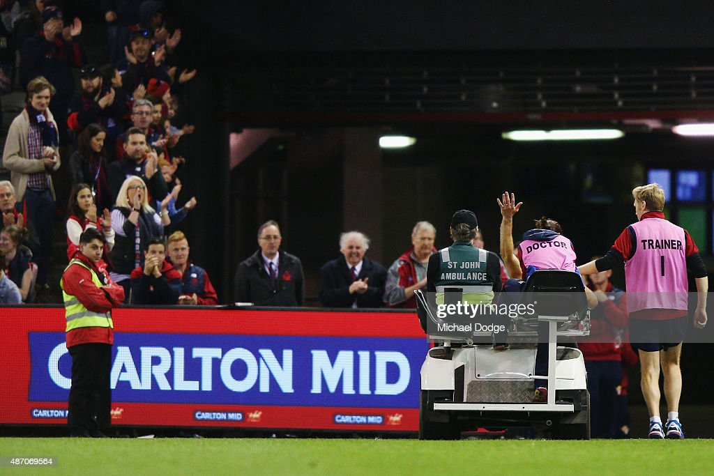 Daniel Cross of the Demons waves to fans as he gets taken off by stretcher after marking the ball during the round 23 AFL match between the Melbourne Demons and the Greater Western Sydney Giants at Etihad Stadium on September 6, 2015 in Melbourne, Australia.