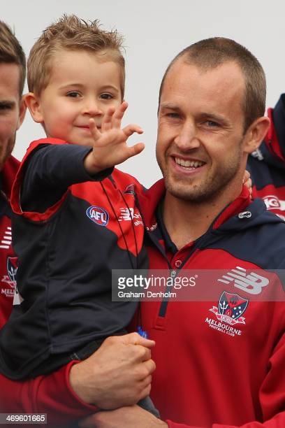 Daniel Cross smiles as he holds his son during Melbourne Demons Family Day at Luna Park on February 16 2014 in Melbourne Australia