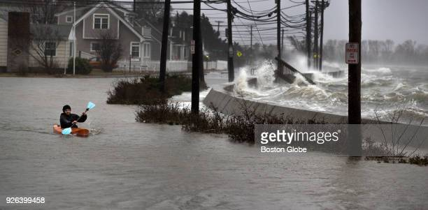 Daniel Cunningham 22 of Quincy dodges waves in his kayak on a flooded E Squantum Street in the Squantum section of Quincy MA during a nor'easter...