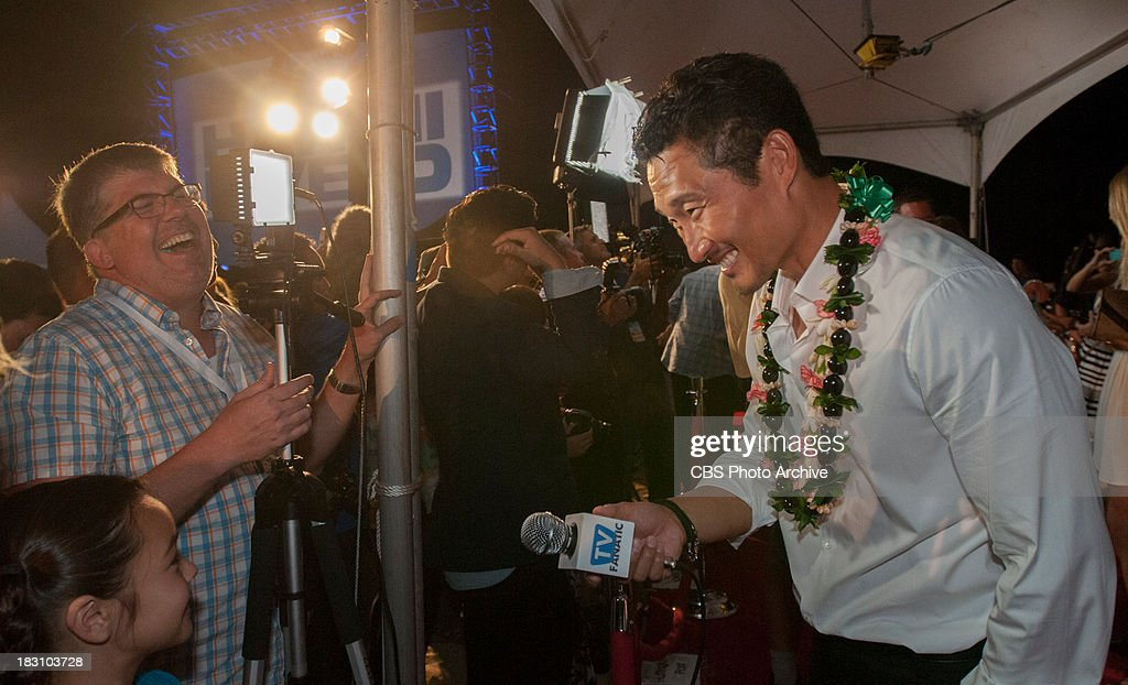 Daniel Dae Kim, who plays the part of Chin Ho Kelly, plays with a microphone at the season four premiere of Hawaii Five-0 on Queen's Beach Thursday, Sept. 26, 2013, in Waikiki, Hawaii. Thousands of Hawaii residents and visitors viewed the first episode on a big movie screen. The show was followed with a concert by the popular boy band group the Jonas Brothers.