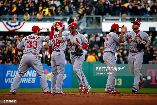 Daniel Descalso and Matt Holliday of the St Louis Cardinals celebrate with their teammates after defeating the Pittsburgh Pirates in Game Four of the...