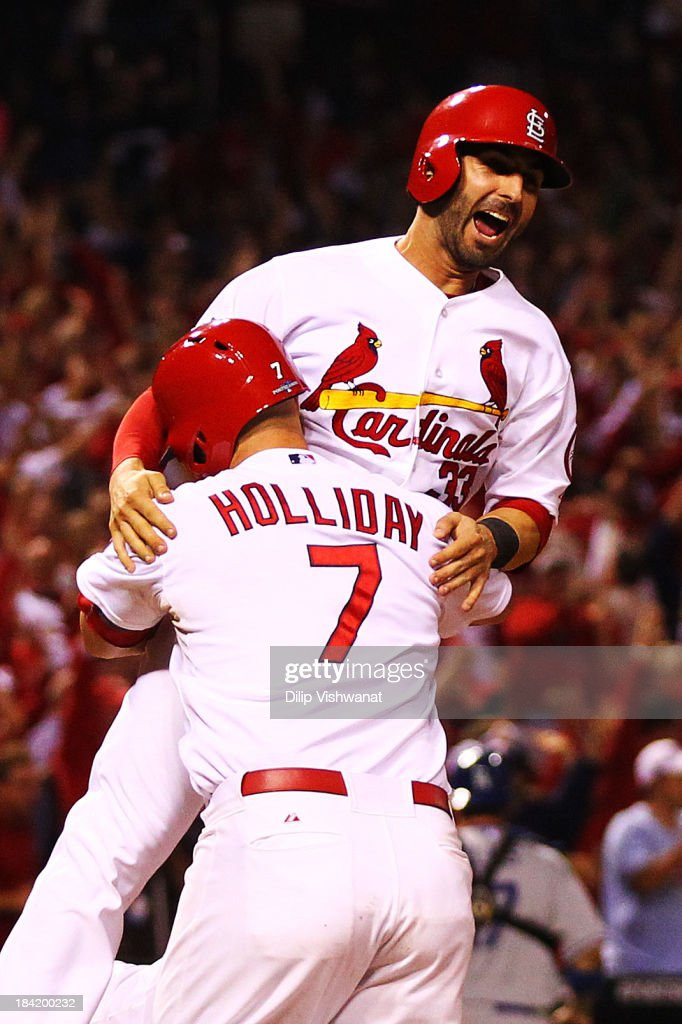Daniel Descalso #33 and Matt Holliday #7 of the St. Louis Cardinals celebrate their to 2 win over the Los Angeles Dodgers in Game One of the National League Championship Series at Busch Stadium on October 11, 2013 in St Louis, Missouri.