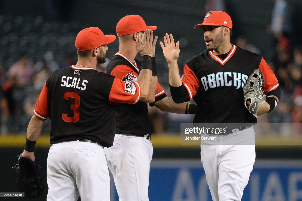 Daniel Descalso #3, Jake Lamb #22 and J.D. Martinez #28 of the Arizona Diamondbacks celebrate after closing out the game against the San Francisco Giants at Chase Field on August 27, 2017 in Phoenix, Arizona.