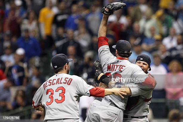 Daniel Descalso Jason Motte and Yadier Molina of the St Louis Cardinals celebrate after they won 126 against the Milwaukee Brewers during Game Six of...