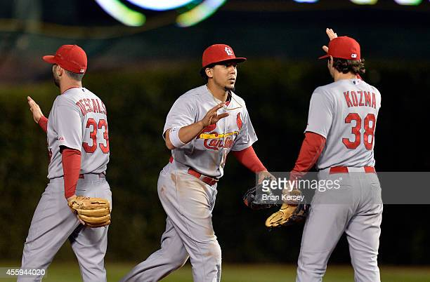 Daniel Descalso Jon Jay and Pete Kozma of the St Louis Cardinals celebrate their win over the Chicago Cubs at Wrigley Field on September 22 2014 in...