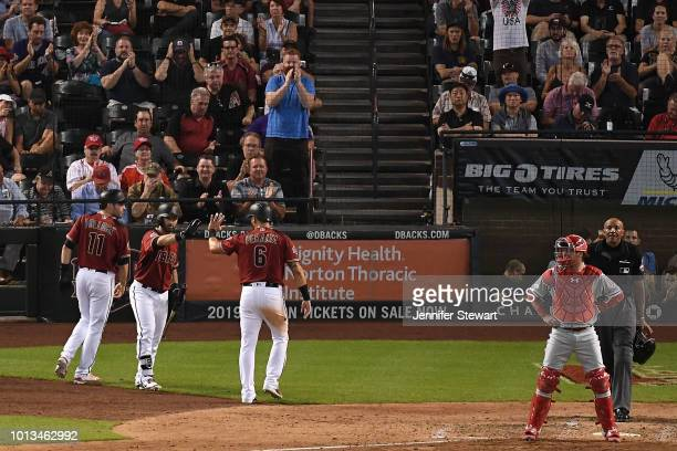 Daniel Descalso of the Arizona Diamondbacks congratulates AJ Pollock and David Peralta after both scoring in the seventh inning of the MLB game...