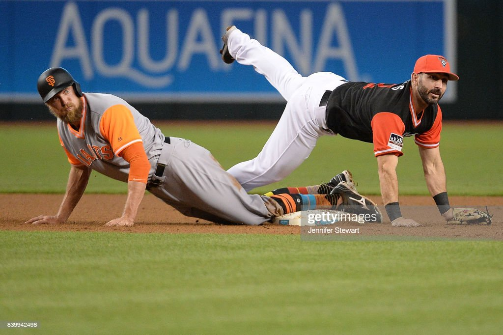 Daniel Descalso #3 of the Arizona Diamondbacks (R) falls over Hunter Pence #8 of the San Francisco Giants after making the force out at second in the first inning at Chase Field on August 27, 2017 in Phoenix, Arizona.