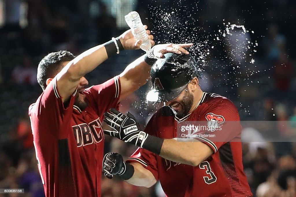 Daniel Descalso #3 (R) of the Arizona Diamondbacks is congratulated by Reymond Fuentes #14 after hitting the game winning RBI single against the Philadelphia Phillies during the MLB game at Chase Field on June 25, 2017 in Phoenix, Arizona. The Diamondbacks defeated the Phillies 2-1 in 11 innings.