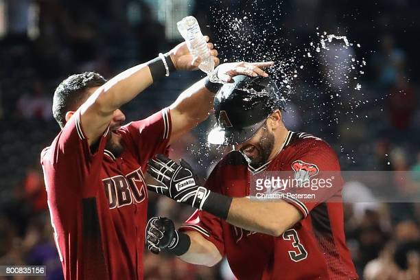 Daniel Descalso of the Arizona Diamondbacks is congratulated by Reymond Fuentes after hitting the game winning RBI single against the Philadelphia...