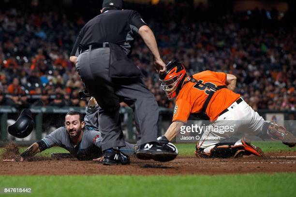 Daniel Descalso of the Arizona Diamondbacks is tagged out at home plate by Nick Hundley of the San Francisco Giants in front of umpire Doug Eddings...