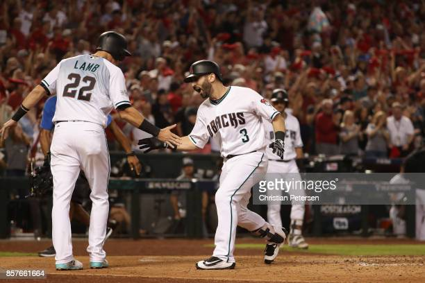 Daniel Descalso of the Arizona Diamondbacks reacts with teammate Jake Lamb after hitting a two run home run during the bottom of the third inning...