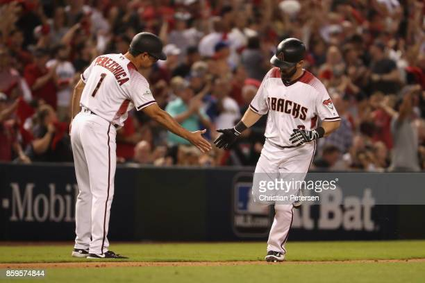 Daniel Descalso of the Arizona Diamondbacks reacts with third base coach Tony Perezchica after hitting a one run home run during the fifth inning of...