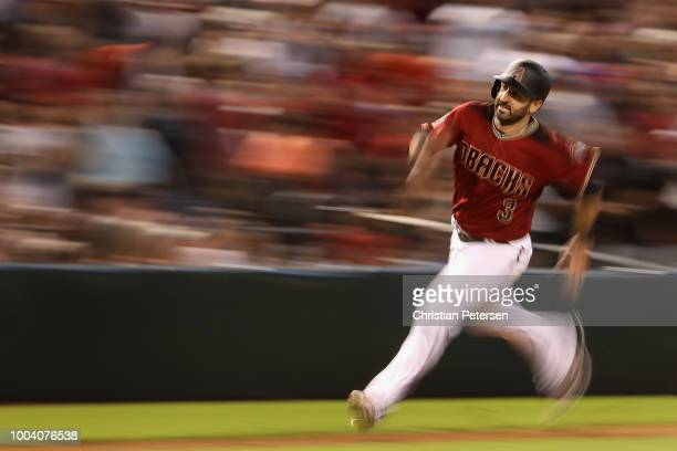 Daniel Descalso of the Arizona Diamondbacks rounds thrid base en route to scoring a run against the Colorado Rockies during the fourth inning of the...