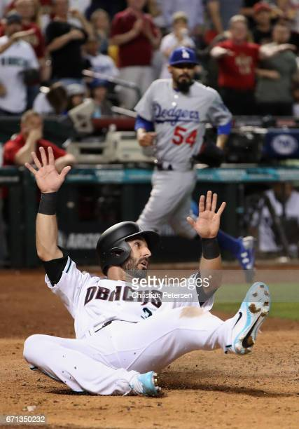 Daniel Descalso of the Arizona Diamondbacks slides in to score a run off releif pitcher Sergio Romo of the Los Angeles Dodgers during the eighth...