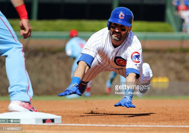 Daniel Descalso of the Chicago Cubs slides safely into third base on an error during the first inning of a game by Dexter Fowler of the St Louis...
