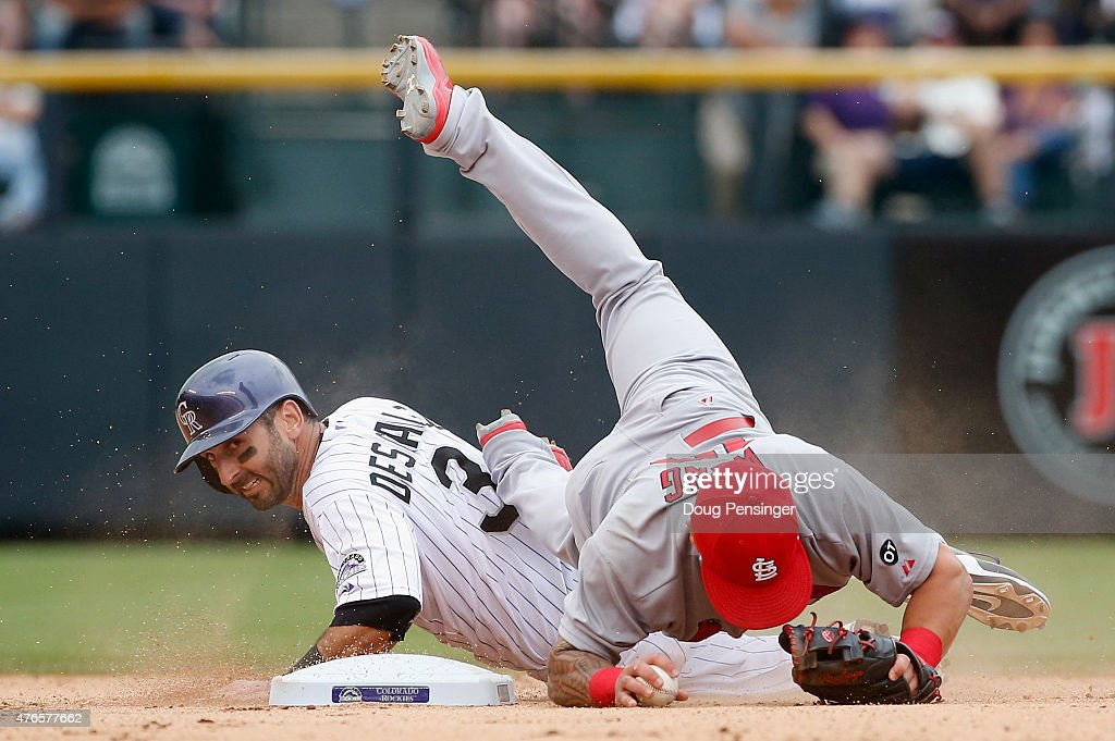 Daniel Descalso #3 of the Colorado Rockies breaks up a double play as he is forced out by second baseman Kolten Wong #16 of the St. Louis Cardinals on a ground ball by Nick Hundley #4 of the Colorado Rockies in the seventh inning at Coors Field on June 10, 2015 in Denver, Colorado.