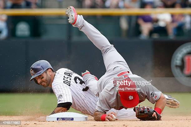 Daniel Descalso of the Colorado Rockies breaks up a double play as he is forced out by second baseman Kolten Wong of the St Louis Cardinals on a...