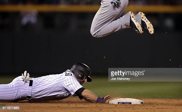 Daniel Descalso of the Colorado Rockies dives safely back to second base as Orlando Arcia of the Milwaukee Brewers hops over the base in the eighth...