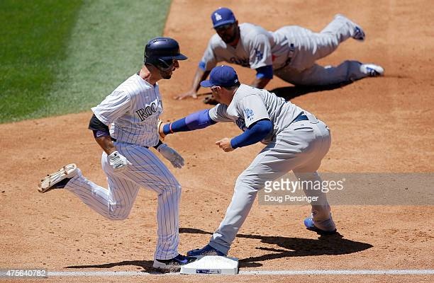Daniel Descalso of the Colorado Rockies is safe at first with an RBI single as second baseman Howie Kendrick of the Los Angeles Dodgers makes the...