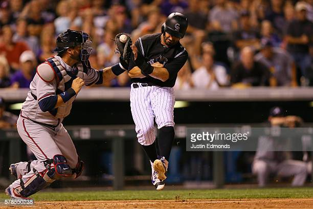Daniel Descalso of the Colorado Rockies is tagged at the plate by catcher AJ Pierzynski of the Atlanta Braves during the eighth inning at Coors Field...