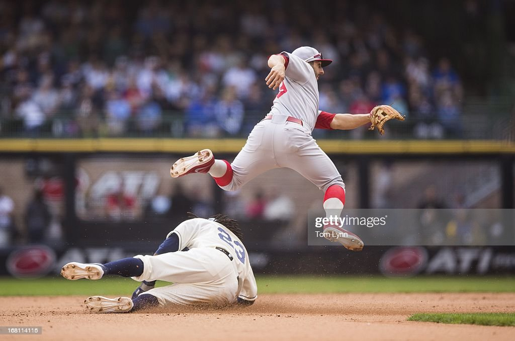 Daniel Descalso #33 of the St Louis Cardinals turns a double play forcing Rickie Weeks #23 of the Milwaukee Brewers at second in the sixth inning at Miller Park on May 5, 2013 in Milwaukee, Wisconsin.