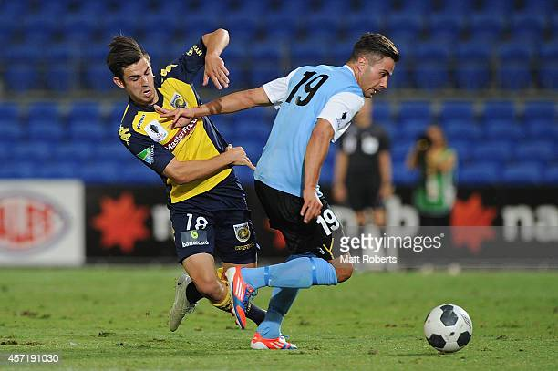 Daniel Dragicevic of the Sharks competes for the ball with Michael Neill of the Mariners during the FFA Cup Quarter Final match between the Palm...