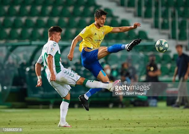 Daniel Escriche Romero of Elche CF competes for the ball with Rafael Marcos Mauro of Cadiz CF during the La Liga Smartbank match between Elche CF and...