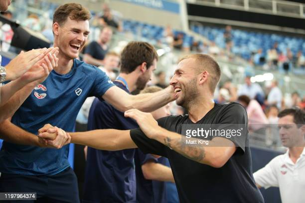 Daniel Evans of Great Britain celebrates with team mate Jamie Murray after winning match point during his Group C singles match against Radu Albot of...