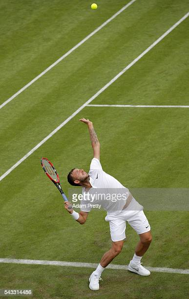 Daniel Evans of Great Britain serves during the Men's Singles first round match against JanLennard Struff on day one of the Wimbledon Lawn Tennis...