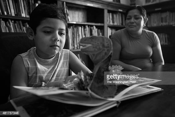 Daniel explores a children's book while in the library at Casa de Maryland with his mother Reyna on August 5 in Langley Park Maryland The family is...