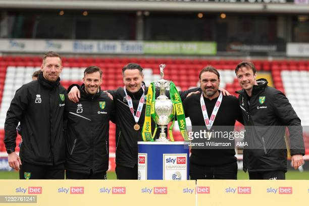 Daniel Farke the head coach / manager of Norwich City and his coaching stand celebrate with the Sky Bet Championship trophy during the Sky Bet...