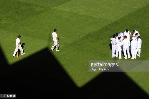 Daniel Flynn and Martin Guptill of New Zealand the field to bat while South Africa players form a huddle during day three of the Third Test match...