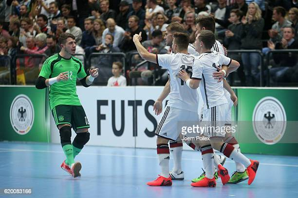Daniel Fredel of Germany celebrates with his team mates after scoring his team's first goal during the Futsal International Friendly match between...