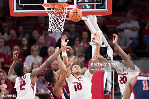 Daniel Gafford Darious Hall and Adrio Bailey of the Arkansas Razorbacks go after a loose ball under the basket against Bruce Stevens of the...
