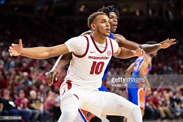 Daniel Gafford of the Arkansas Razorbacks looks for a pass while being defended by Dontay Bassett of the Florida Gators at Bud Walton Arena on...