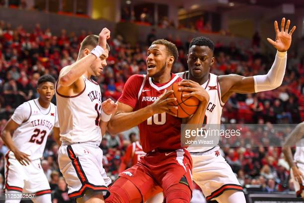 Daniel Gafford of the Arkansas Razorbacks looks for a shot against Matt Mooney and Norense Odiase of the Texas Tech Red Raiders during the game on...