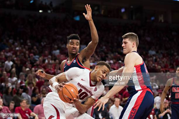 Daniel Gafford of the Arkansas Razorbacks tries to get a shot off against Bruce Stevens and Justas Furmanavicius of the Mississippi Rebels at Bud...