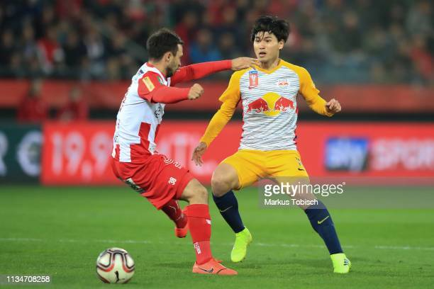 Daniel Geissler of Grazer AK competes for the ball with Takumi Minamino of RB Salzburg during the UNIQA OeFB Cup Semifinal match between Grazer AK...