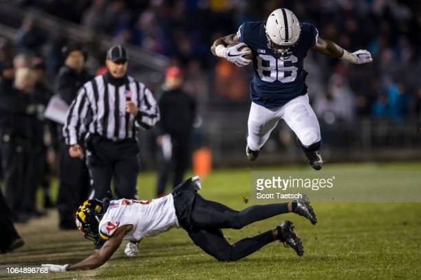 Daniel George of the Penn State Nittany Lions hurdles RaVon Davis of the Maryland Terrapins during the first half at Beaver Stadium on November 24...